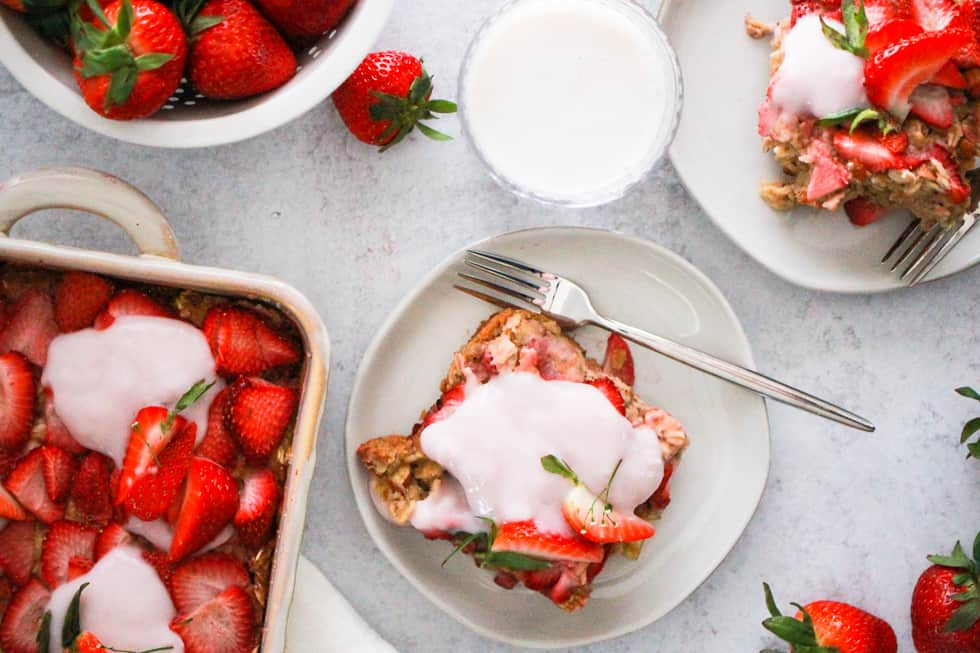 Horizontal overhead image of baked strawberry oatmeal with almond milk.