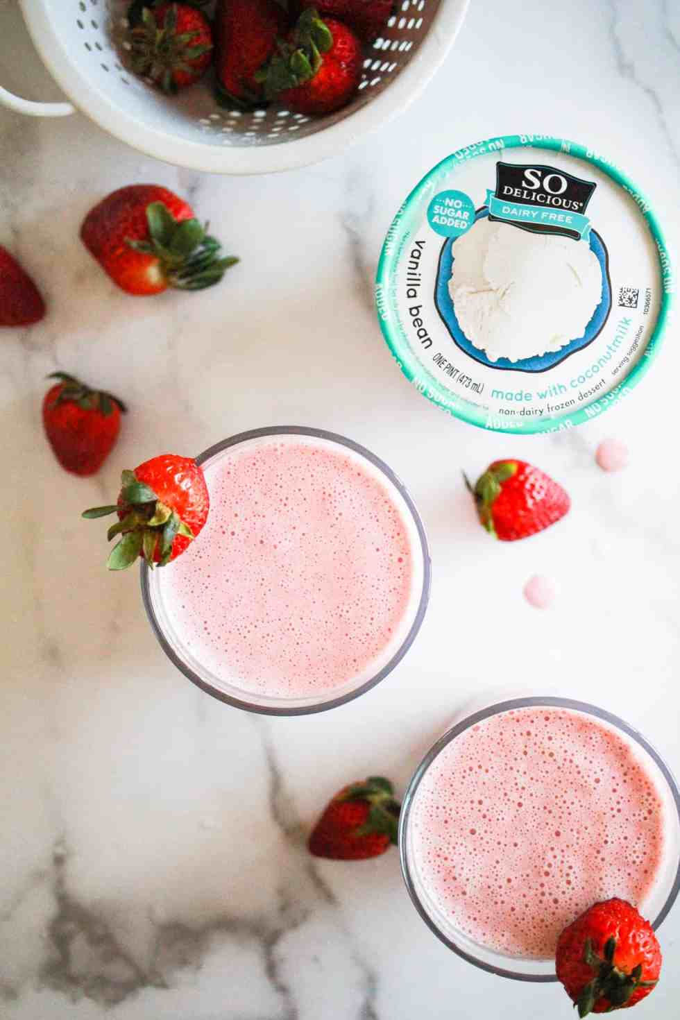 Two strawberry milkshakes with a pint of So Delicious Coconutmilk Ice Cream Alternative and fresh strawberries.