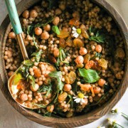 Israeli couscous salad in wooden bowl with blue and gold spoon.