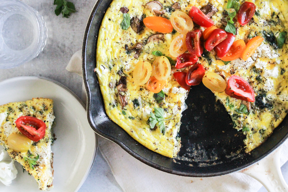 Horizontal image of a frittata topped with tomatoes in a skillet with once slice on a plate.