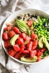 White bowl of watermelon poke with edamame and avocado.