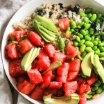White bowl of watermelon poke with edamame and avocado.