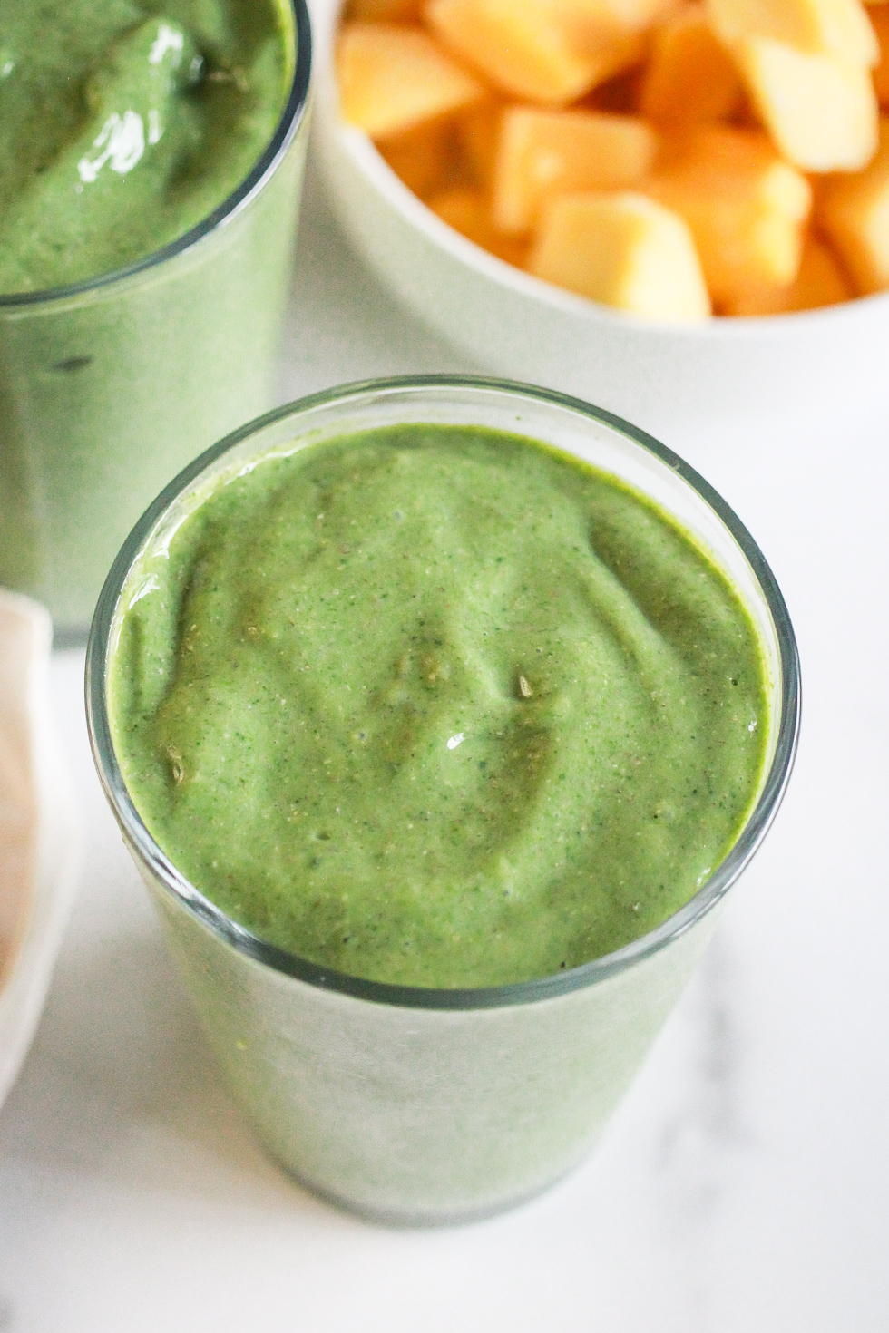 Green smoothies next to a bowl of frozen mangoes