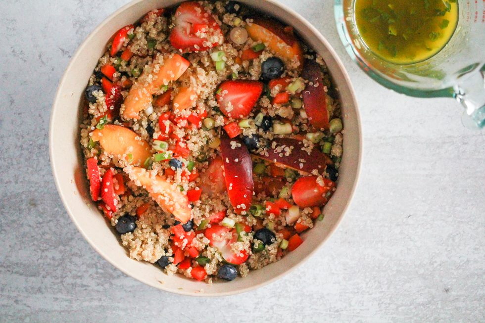 Horizontal image of fruit salad with quinoa and lemon dressing in glass measuring cup.