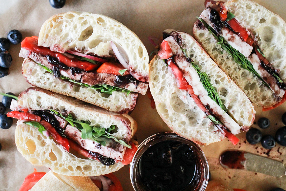 Horizontal image of two halved sandwiches with blueberry balsamic sauce in a glass jar.