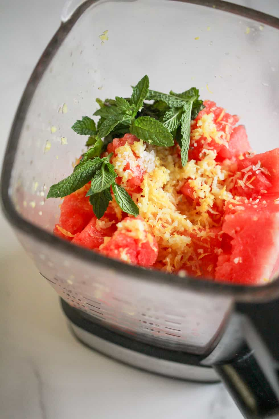 Blender filled with watermelon, lemon zest, and fresh mint.