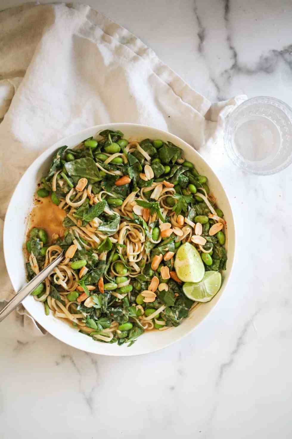 Overhead image of pad Thai-style noodles on white marble countertop.