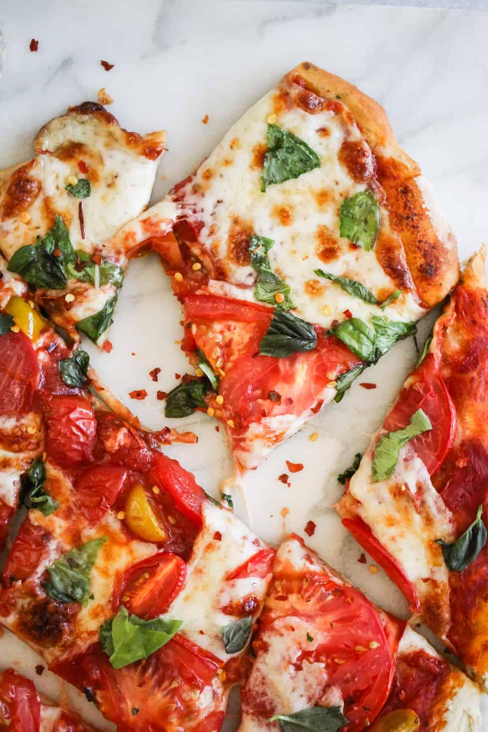 Sliced of vegetable pizza on white marble slab.