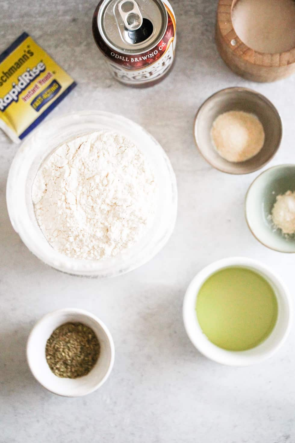 Ingredients for pizza dough, including flour, beer, oil, and instant yeast, on a grey counter.