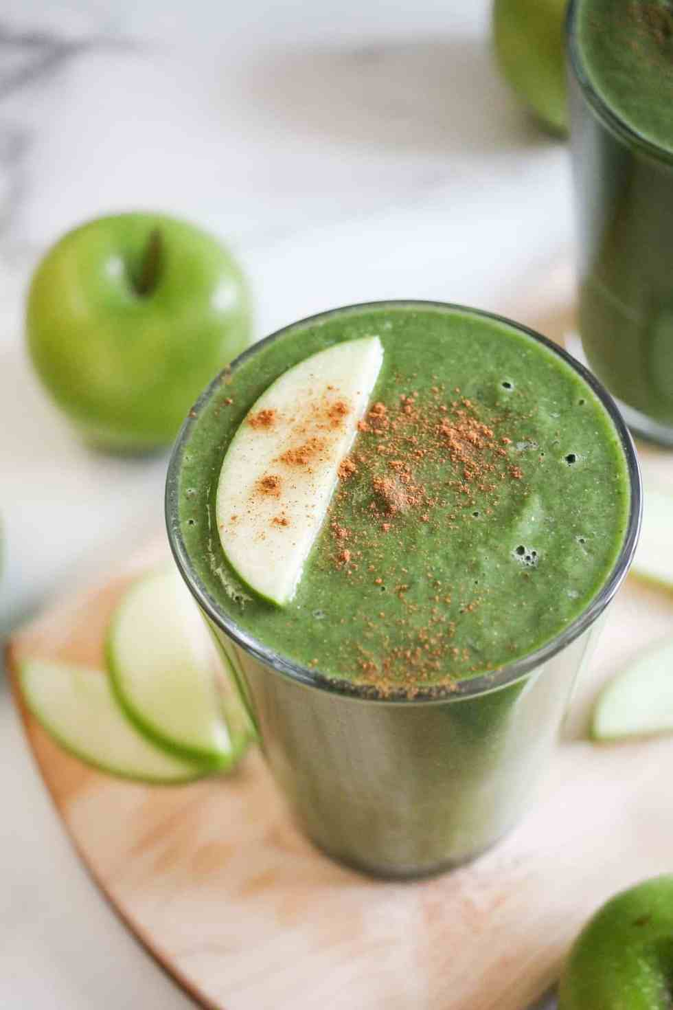 Green apple lentil smoothie in a glass garnished with apple slice and cinnamon.