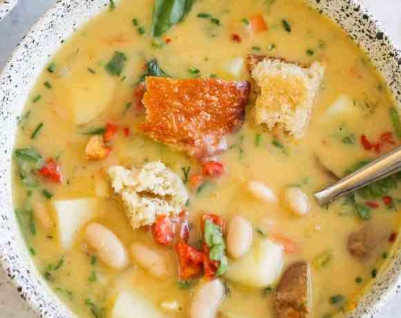 Vegan potato soup in white ceramic bowl against gray background.
