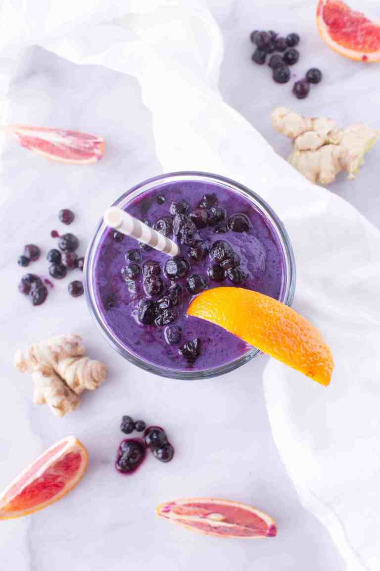 Overhead image of blueberry smoothie made with silken tofu with blood orange wedge garnish.