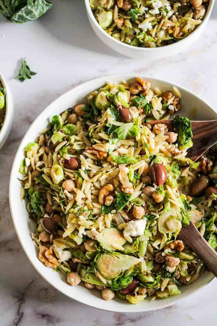 Closeup image of orzo salad with brussels sprouts and olives in a white bowl with wood serving spoons.