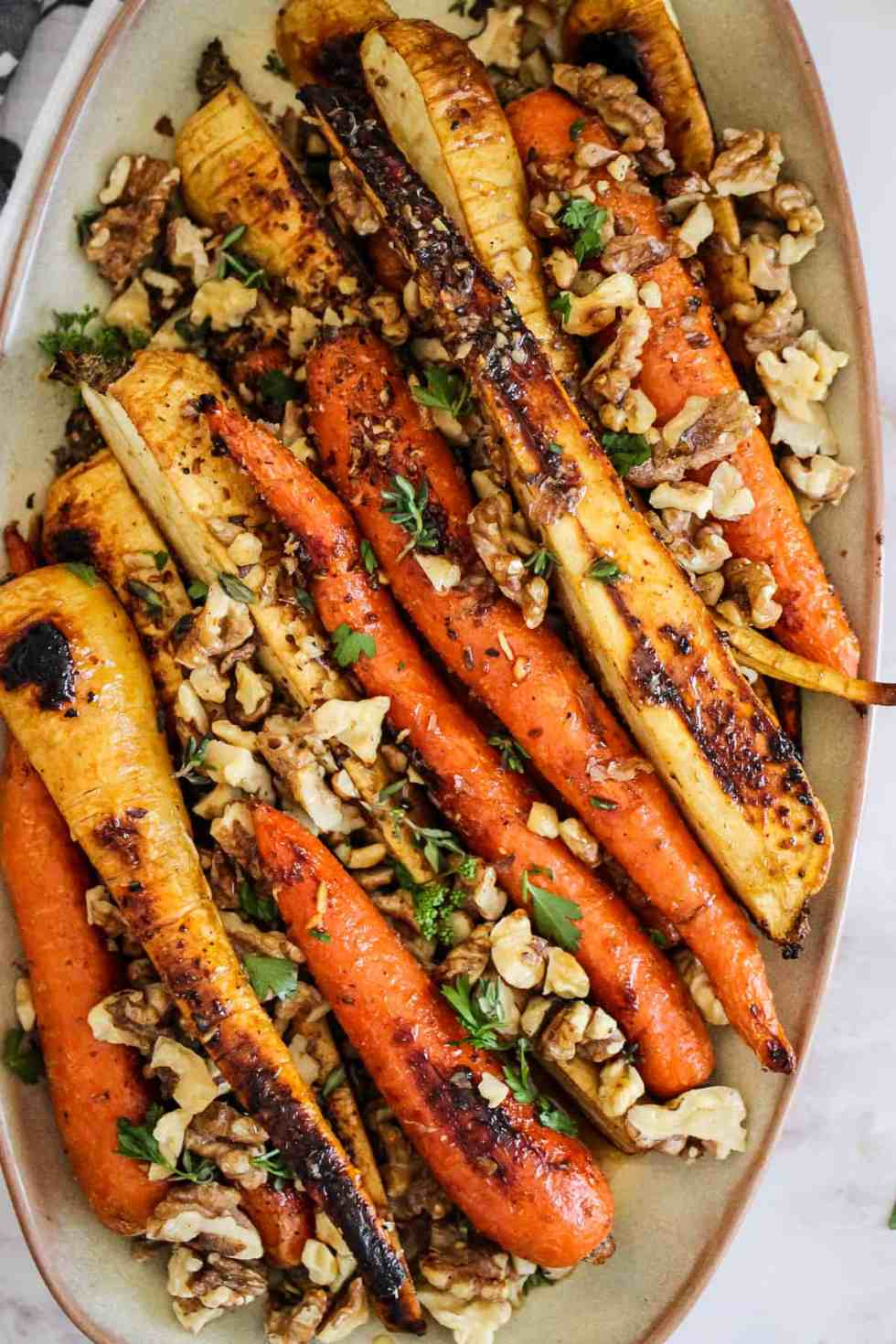 Honey roasted carrots and parsnips on beige serving platter with walnuts and fresh herbs.