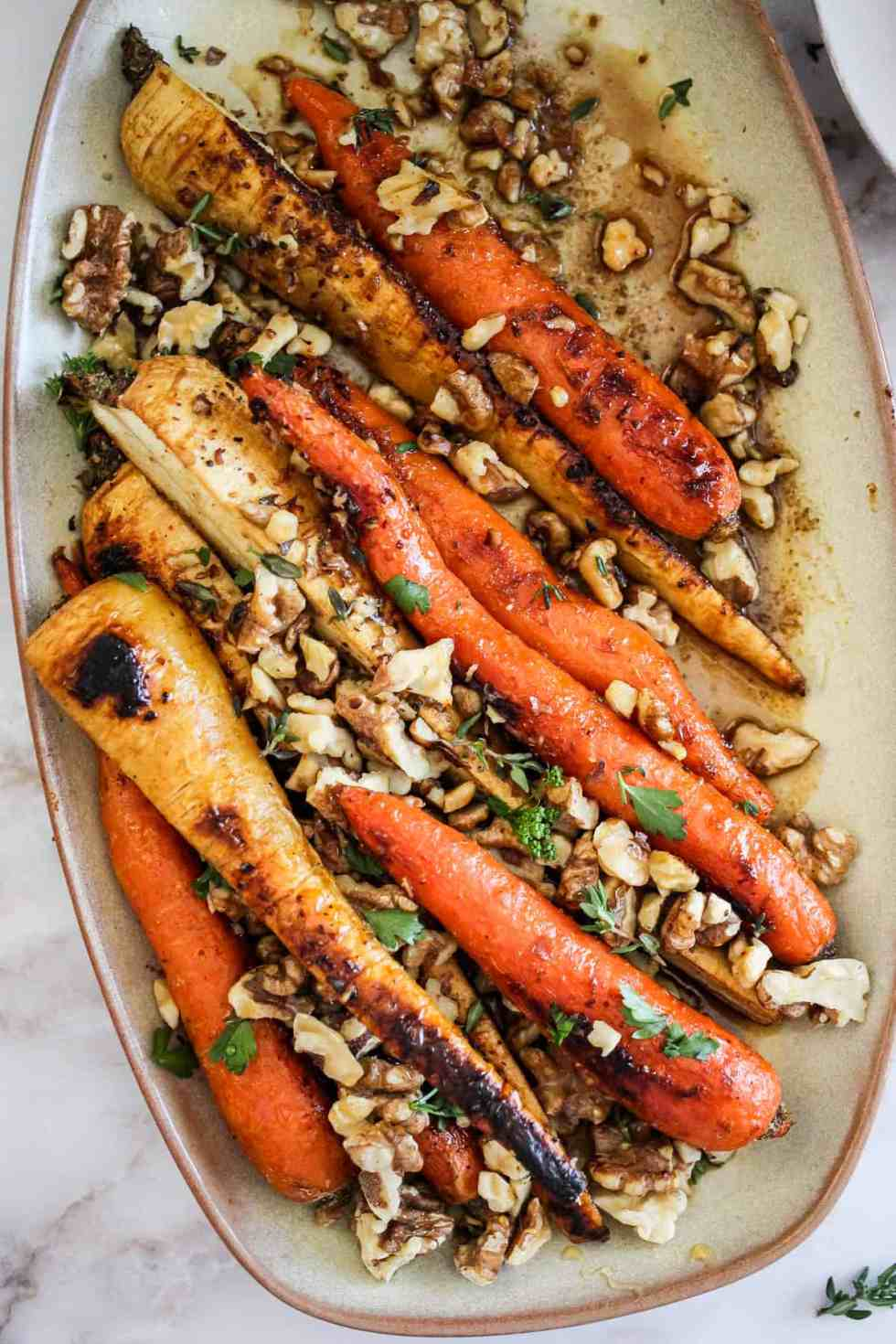 Overhead image of roasted carrots and parsnips on a beige serving platter.