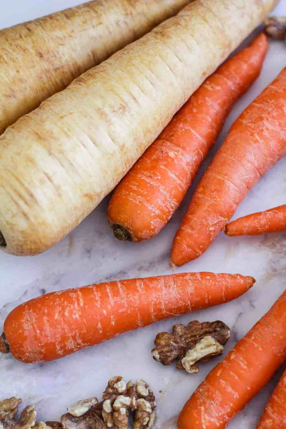 Whole parsnips, whole carrots, and walnuts on white marble.