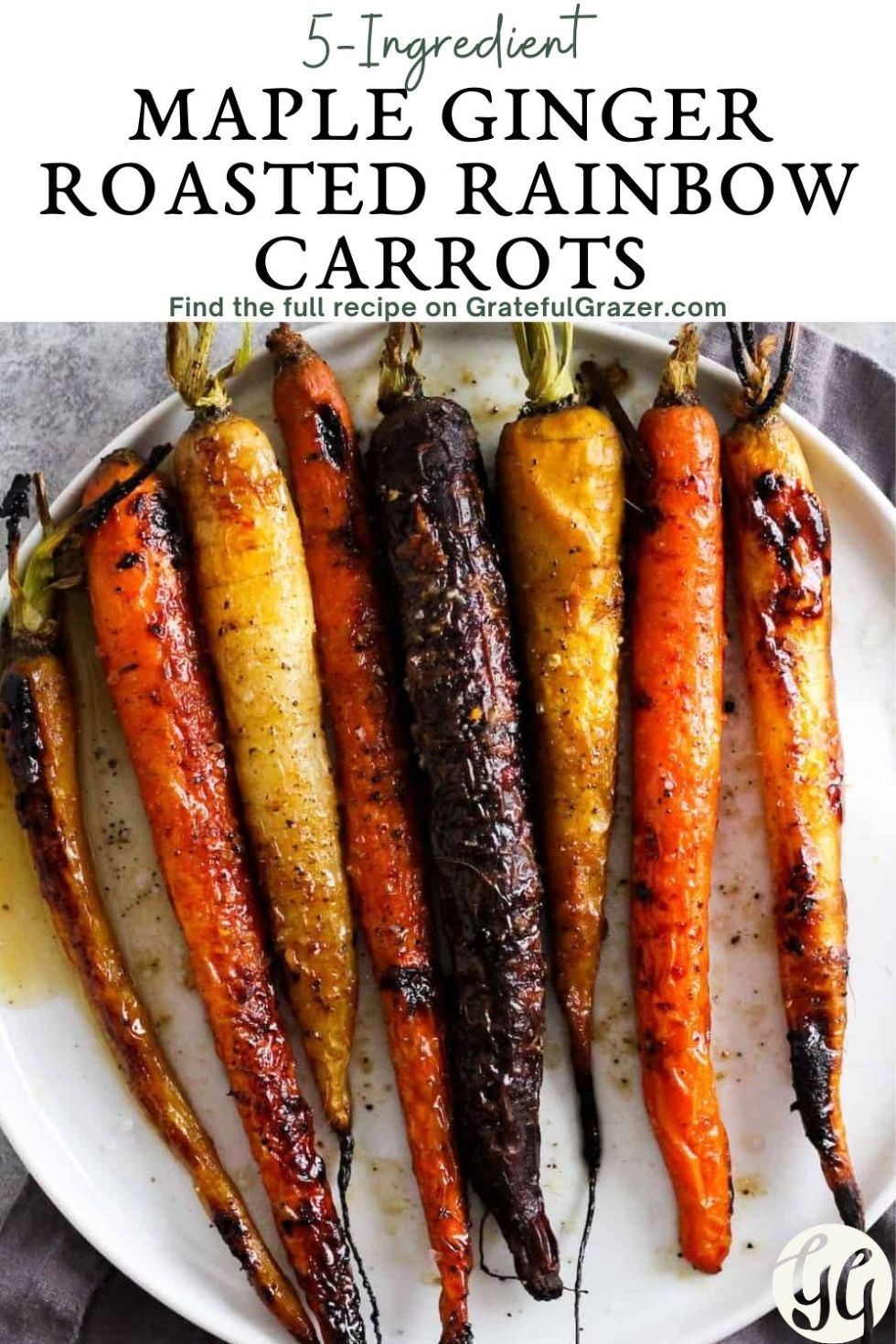 "Roasted rainbow carrots on a white plate with text reading, ""5-Ingredient Maple Ginger Roasted Rainbow Carrots. Find the full recipe on GratefulGrazer.com"""