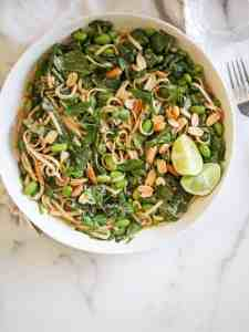 peanut noodles with spinach in a white bowl.