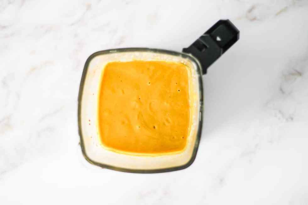 Overhead image of yellow curry sauce in a blender.