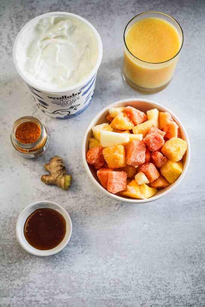 Yogurt, orange juice, frozen fruit, turmeric, ginger, and honey on a gray background.