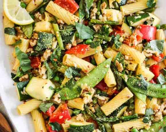Vegan Pasta Primavera with colorful vegetables on a white serving platter.