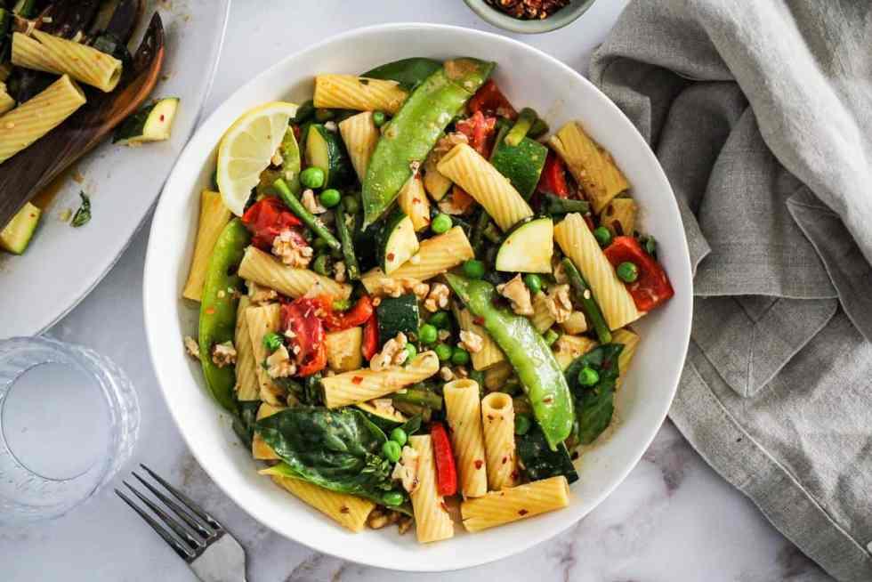 Horizontal overhead image of vegan pasta primavera in a white bowl with a linen napkin.