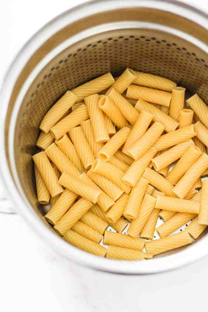 Cooked rigatoni pasta in a metal strainer.