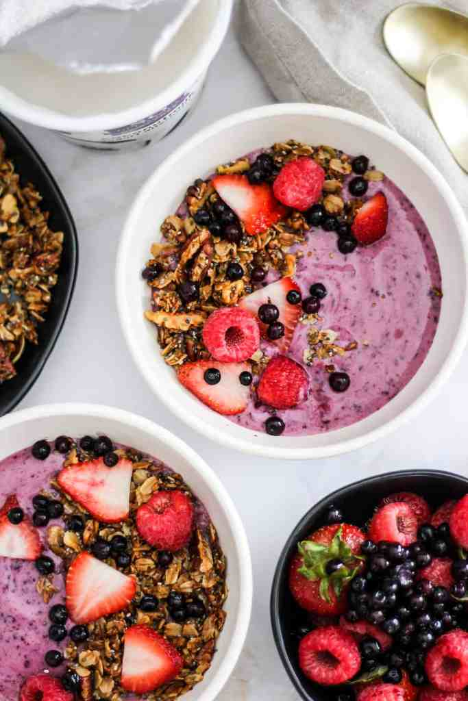 Overhead image of blueberry yogurt bowls topped with berries and granola.