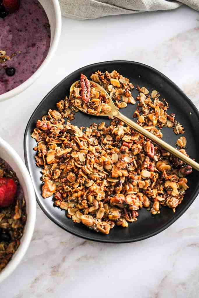 Homemade granola on a black plate with a gold spoon.