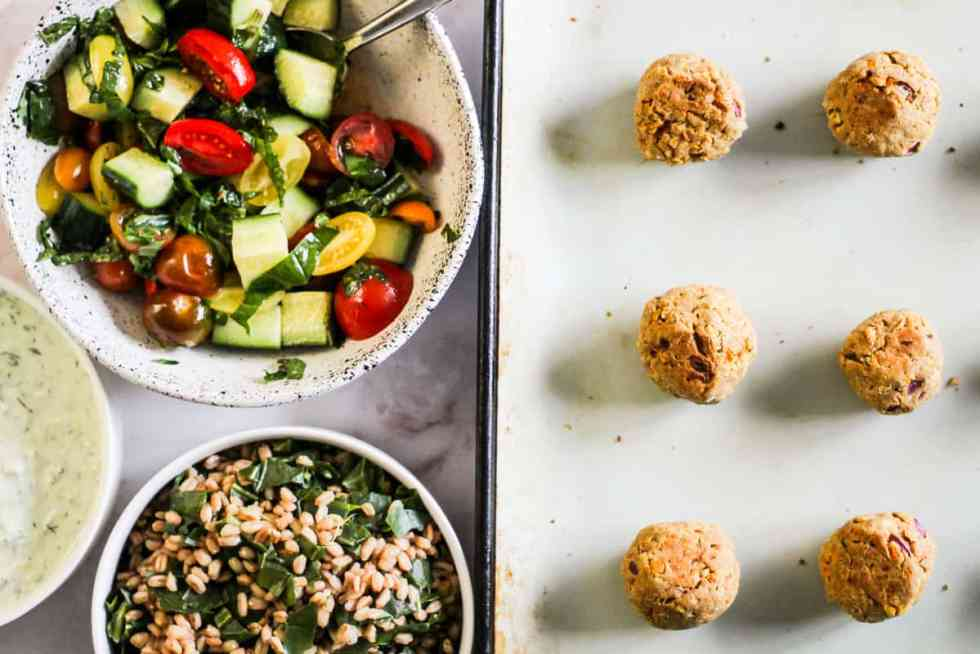 Falafel on a baking sheet with a bowl of tomato-cucumber salad, a bowl of collard greens farro, and tzatziki sauce.