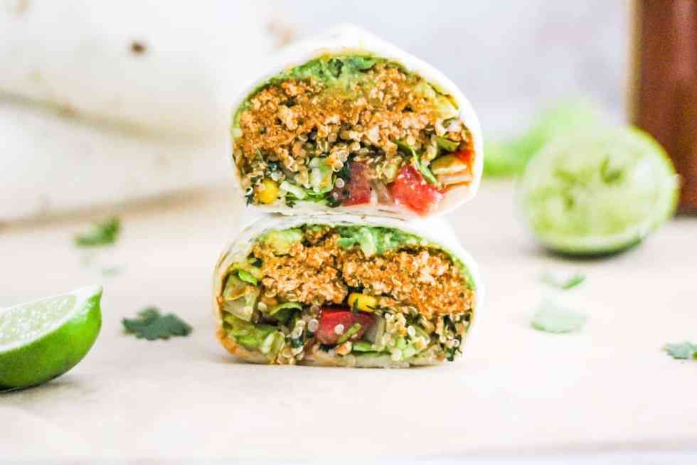 Horizontal image of a sofritas tofu burrito with one half stacked on top of the other.
