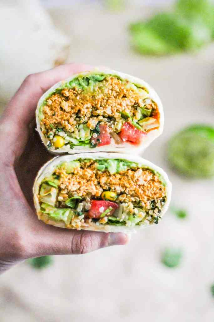 Hand holding a tofu and quinoa burrito with avocado sliced in half.