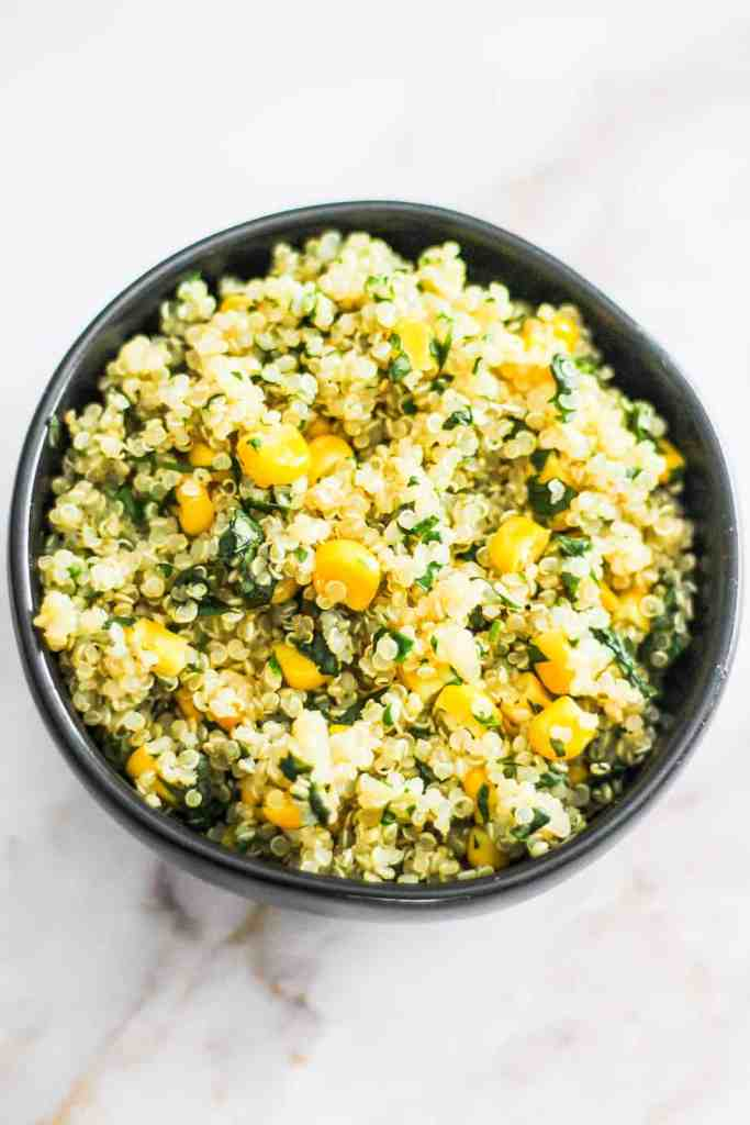 Corn, quinoa, and cilantro in a black bowl.
