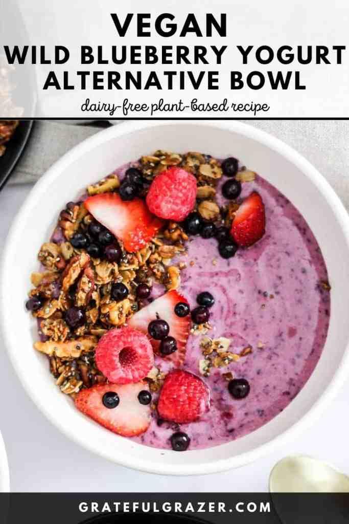 "Wild blueberry vegan yogurt in a white bowl with granola and fruit. Text reads, ""Vegan Wild Blueberry Yogurt Alternative Bowl; dairy-free plant-based recipe; GratefulGrazer.com."""