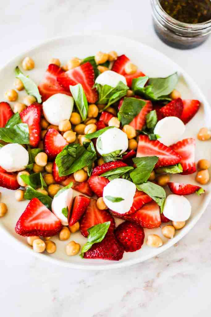 Sliced strawberries, mozzarella, chickpeas, and basil on a white plate.