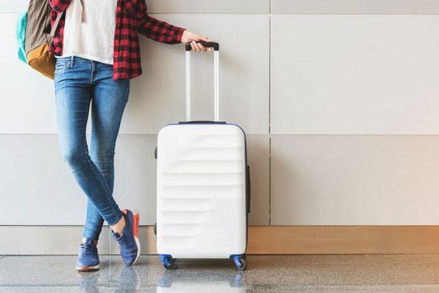 femeie carand un bagaj alb, gata de calatorie