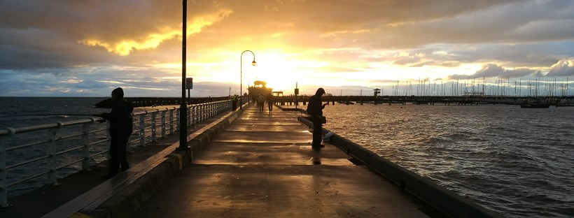 Person standing on a pier at sunset