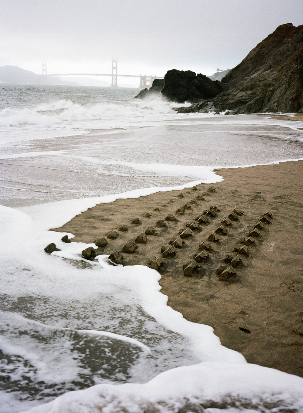 """For the first part of this series, Wright created a mould in the form of an L-shaped suburban dwelling, and set out a series of sand castles on his local beach. This scale-model suburbia was washed away by the tide, which perhaps urges us to consider the relative transience of so solid a symbol of the American dream, particularly since the 2007 subprime mortgage collapse. "" Artist's statement: ""In Master Plan, I am conflating a child's sandcastle with architecture typifying postwar American suburbia. This three-part series culls artifacts from my childhood, investigating suburbia in its vision and legacy.Phase One focuses on the mass-produced tract house, re-examining it as symbol for the model American Dream."""