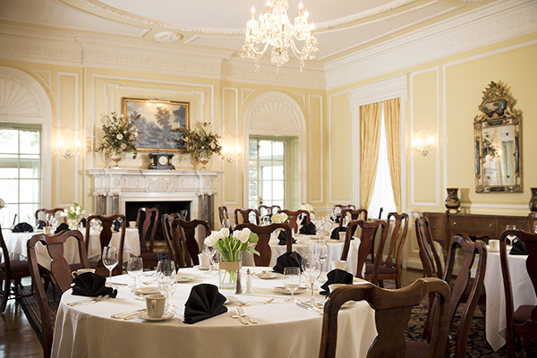 Brightly lit yellow dining room style with antique crown molding, chandelier and other decorative items. Several tables with white tablecloths, Queen Anne style wooden chairs and white tulip flower arrangements in the center of each table