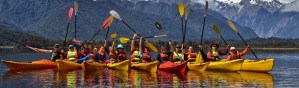 photo of numerous kayakers in a fjord