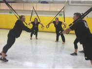Five people are suspended by TRX equipment in the fieldhouse.