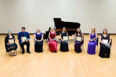 Seven young women and one young man, many holding bouquets and plaques, sit on a stage in front of a grand piano.
