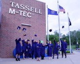 Adult Education graduates toss their caps in the air outside the Tassell M-TEC.