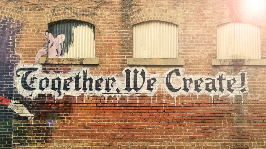 Brick Wall that has graffiti stating Together We Create