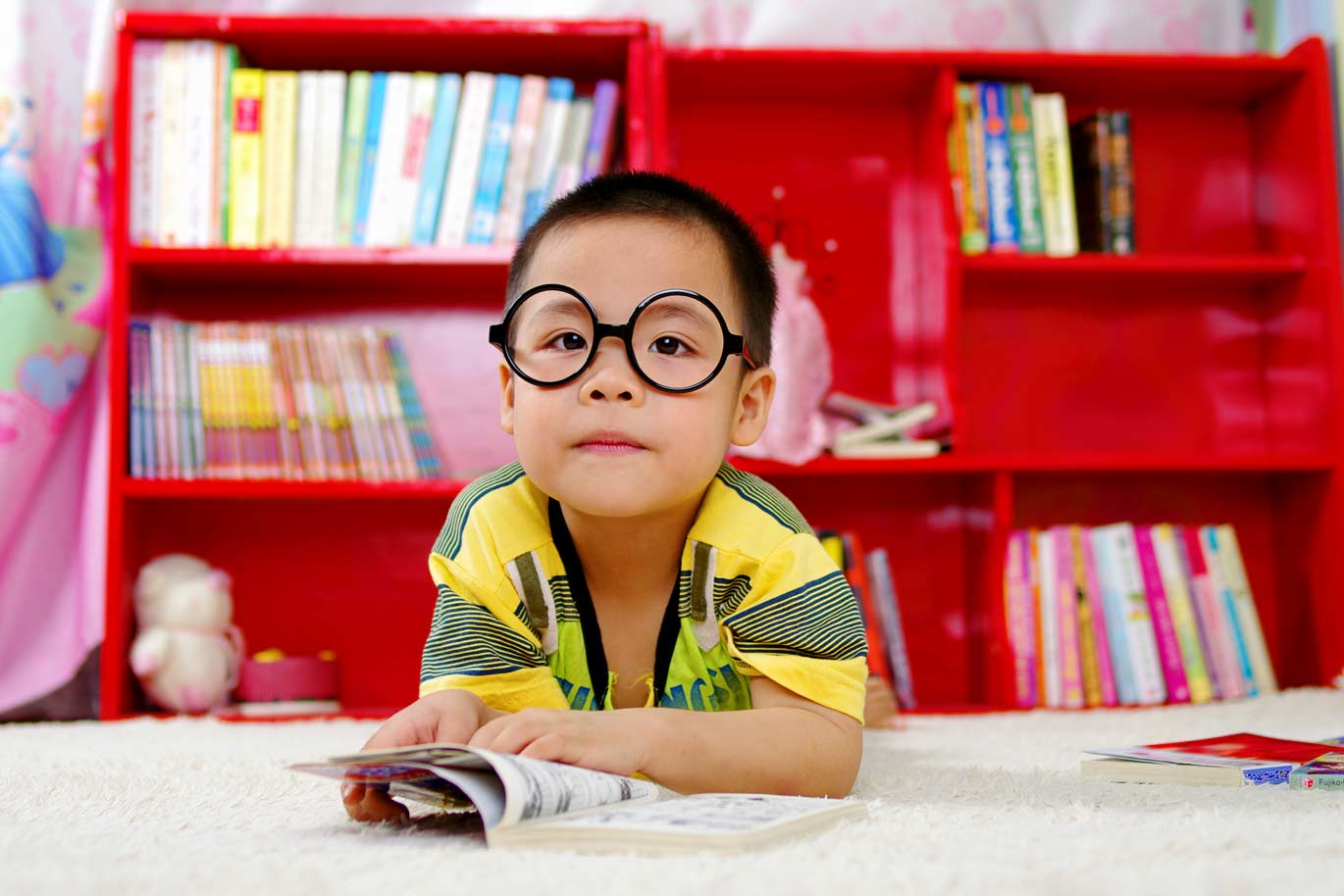 Young Asian boy with glasses reading on a rug in front of a red bookcase