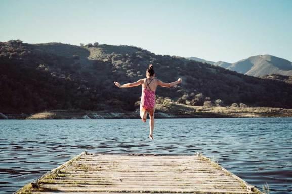 Summer overnight camp fun, girl jumping into a lake