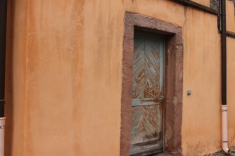 Paint on a wooden door has flaked off along the grain, creating a subtle pattern.