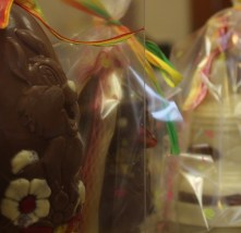 A very happy bunny sit by a pair of chocolate bells