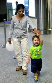 Moshe Holtzberg leads Sandra Samuel through Mumbai airport for flight to Israel where parents were buried.
