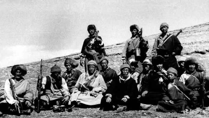 """The Dalai Lama (front right center, in black, wearing glasses) poses with his armed guerrilla escort as he flees Tibet after having instigated a militarily futile """"uprising"""" of monks against the revolutionary Chinese government's overthrow of his feudalist theocratic rule. Date unknown."""